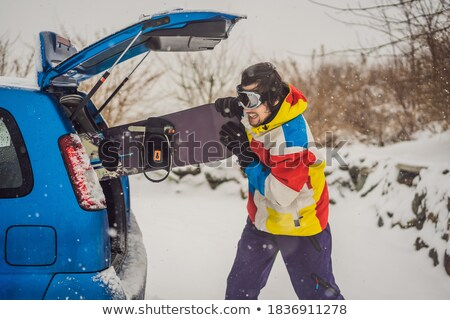 The snowboard does not fit into the car. A snowboarder is trying to stick a snowboard into a car. Hu Stock photo © galitskaya