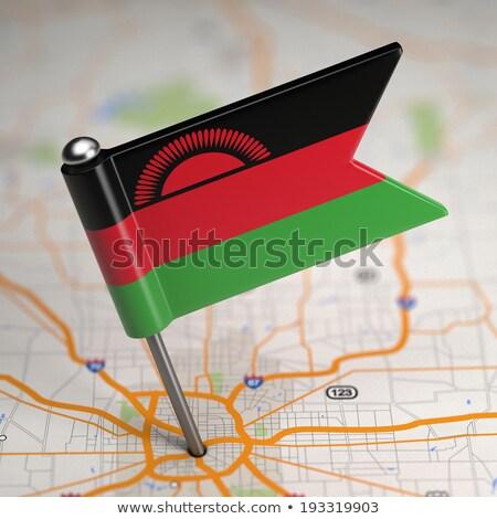 Malawi Small Flag on a Map Background. Stock photo © tashatuvango
