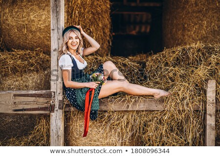 Young blond woman sits on hay Stock photo © Aikon