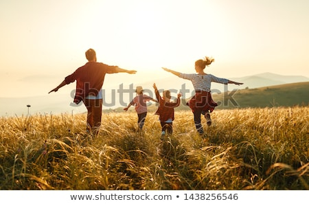 Happy family, father, mother, son and daughter in nature, sunset Stock photo © zurijeta