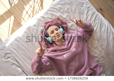 Happy excited young woman lying with eyes closed  Stock photo © deandrobot
