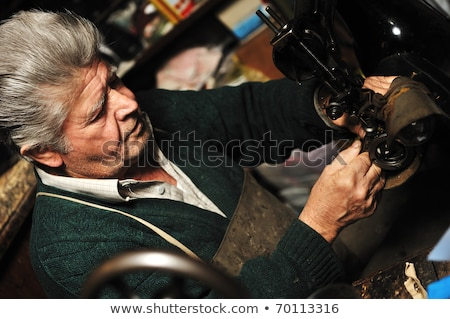 Senior man working with old machine in his own workshop stock photo © zurijeta