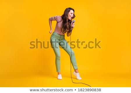 Stock photo: Beautiful woman singing karaoke song with microphone