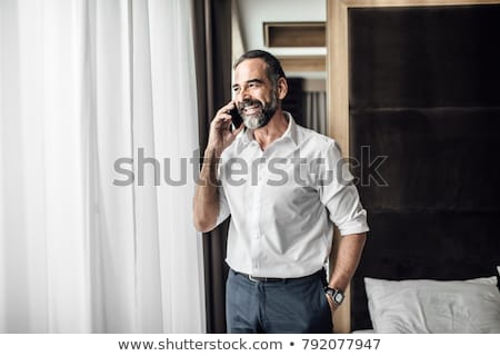 Man talking on cell phone in bed Stock photo © IS2