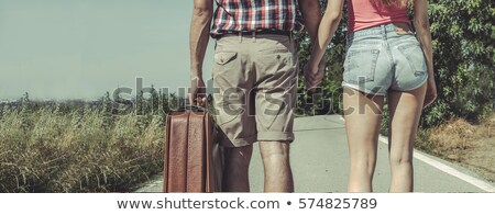 Bride carrying suitcase on country road Stock photo © IS2