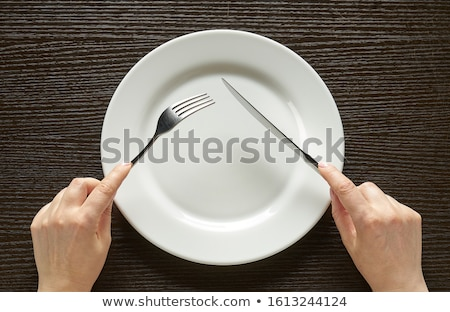 knife and fork with white plate on wooden table stock photo © inxti