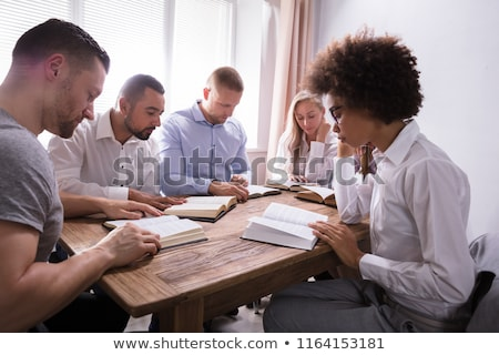 man praying with bible over wooden desk stock photo © andreypopov