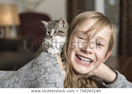 Preteen girl of 10 years old with her cat pet on the sofa Stock photo © Lopolo
