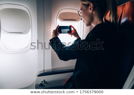 Young woman taking photos during flight in a modern airplane Stock photo © lightpoet