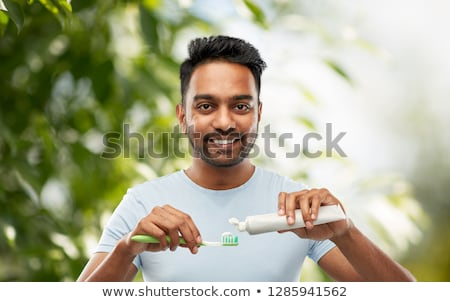 indian man cleaning teeth over natural background Stock photo © dolgachov