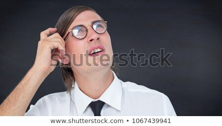 Stock photo: Close up of nerd man scratching head against navy chalkboard