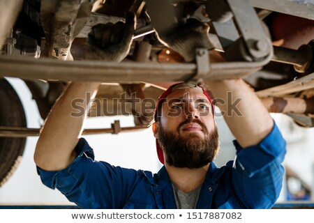 Bearded worker of technical service concentrating on examination of car engine Stock photo © pressmaster