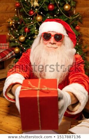 Happy Santa in glamorous heartshaped sunglasses passing you giftbox Stock photo © pressmaster