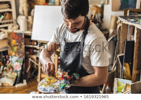Modern painter in apron holding palette with mixed colors and paintbrush Stock photo © pressmaster