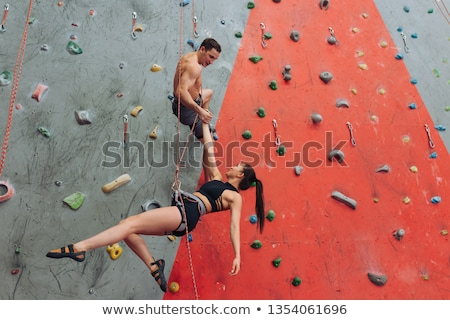 Young woman in climbing equipment moving up while holding by artificial rocks Stock photo © pressmaster
