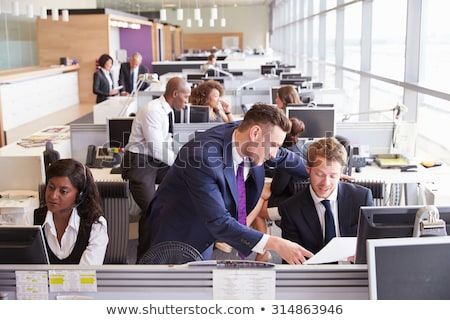 Front view of busy multi-ethnic business colleagues discussing about the strategy on a flip chart bo Stock photo © wavebreak_media