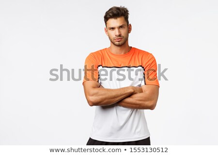 Serious masculine man with bristle, wear sports t-shirt, cross arms over chest, squinting, look came Stock photo © benzoix
