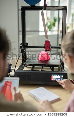 Pink round 3d object is being printed while young woman touching button on panel Stock photo © pressmaster