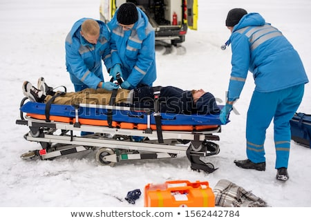 Two young paramedics in workwear fixing unconscious man with belts on stretcher Stock photo © pressmaster