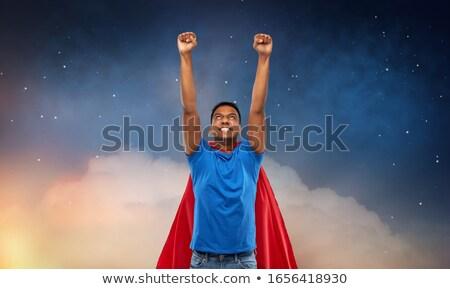 man in red superhero cape flying over night sky Stock photo © dolgachov