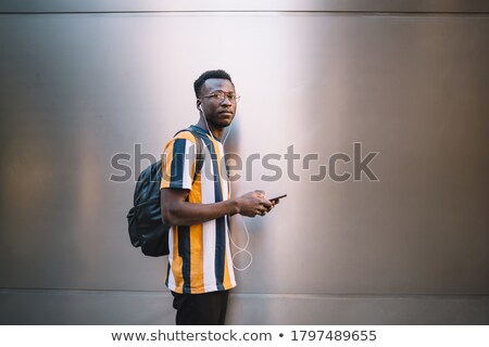 Serious guy scrolling in smartphone while listening to music during work Stock photo © pressmaster