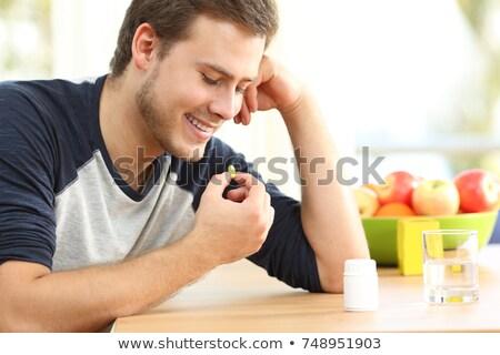 Fiatalember eszik omega3 tabletta víz hal Stock fotó © Lopolo