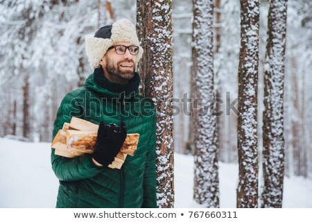 Pleasant looking happy male holds firewood, looks thoughtfully aside, stands near winter trees, drea Stock photo © vkstudio