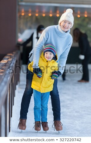 young mother teaching her little son ice skating at outdoor skating rink. Family enjoy winter on ice Stock photo © galitskaya