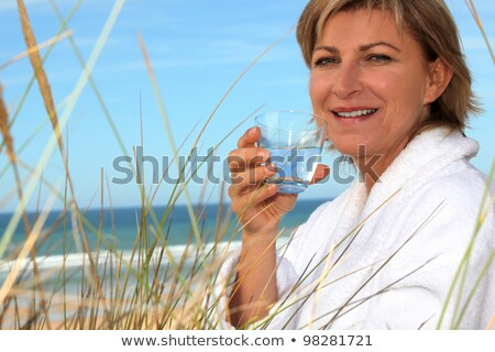 Woman drinking a glass of water on a sand dune Stock photo © photography33