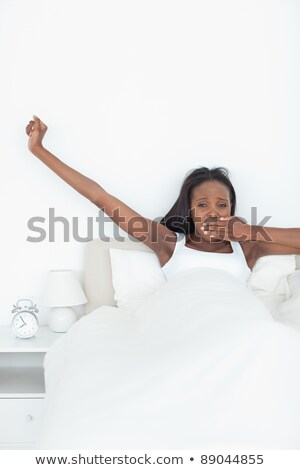 Young woman yawning and stretching her arms while waking up in her bedroom Stock photo © wavebreak_media