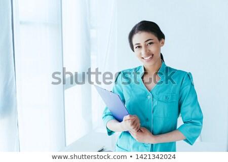 Nurse looking at camera while holding a clipboard in hospital ward stock photo © wavebreak_media