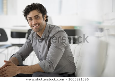 seated young business man leaning forward stock photo © feedough