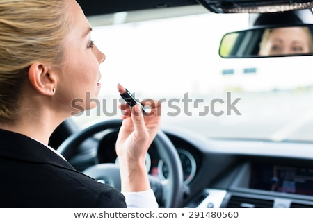 woman applying makeup while in the car stock photo © witthaya