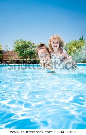 Ninos jugando a cuestas piscina diversión agua Foto stock © meinzahn