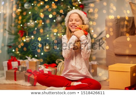 cute little girl in a santa hat hugging a teddy stock photo © stryjek