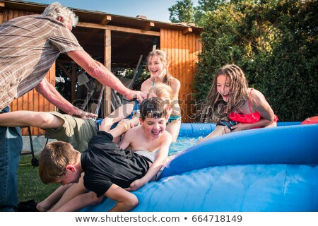 grandfather playing with his grandson in a swimming pool stock photo © d13