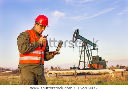Stock photo: Pumpjack Oil Pump And Protective Helmet
