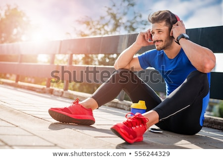handsome young man listening to music after running stock photo © nenetus