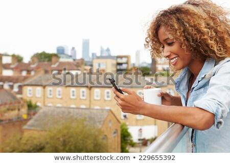 женщину питьевой кофе телефон балкона смартфон Сток-фото © Kzenon