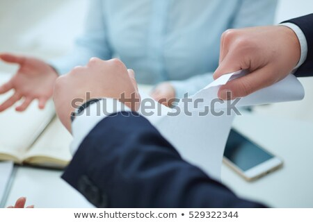 Breaking contract. Furious young woman tearing up paper Stock photo © artfotodima