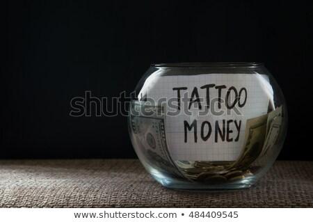 Glass jar witn money for tattoo stock photo © Natali_Brill