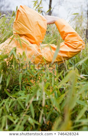 man in raincoat within plants looking Stock photo © IS2