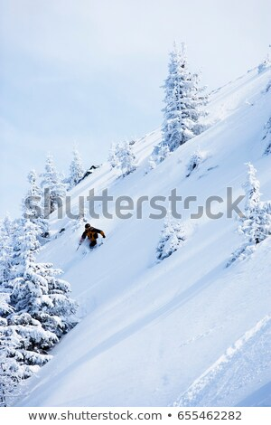 Man in black & orange outfit off-piste. Stock photo © IS2