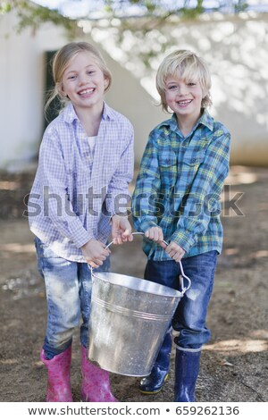Children carrying heavy pail outdoors Stock photo © IS2