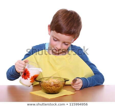 boy pouring milk over cereal stock photo © is2
