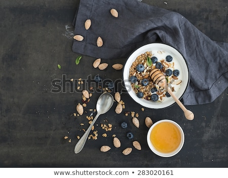 Fresh ripe fruits, blueberry, almond nuts, oat flakes, crisps on a plate on a gray background. Stock photo © artjazz