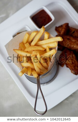 French fries and chicken wings on parchment Stock photo © dash