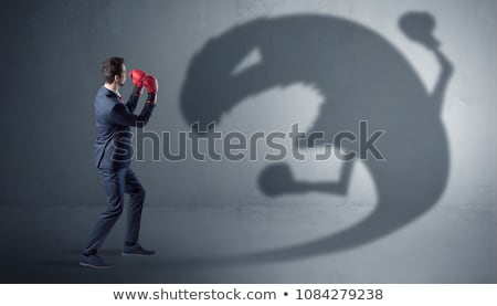 Businessman fighting with a big monster shadow Stock photo © ra2studio