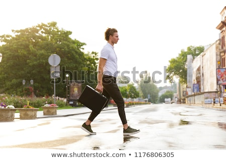 Zijaanzicht ernstig gekruld zakenman aktetas lopen Stockfoto © deandrobot
