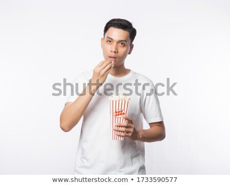 portrait of a smiling young asian man holding popcorn stock photo © deandrobot